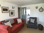 Lounge with large comfy sofa. Warm and cosy with the log burner in winter, cool & light in summer