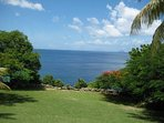 Sweeping green grounds lead up to the ocean below with views of the island of Redonda and Nevis.