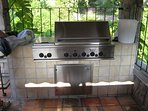 The property has a stainless steel GE propane fueled multi-burner grill, outdoor refrigerator, and bar.