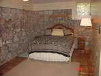 Guest bedroom with cooling stone walls, air conditioning, and queen bed.