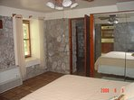 Master bedroom with king sized bed and air conditioning.