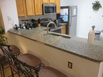 Fully equipped kitchen with quartz counter top and bar