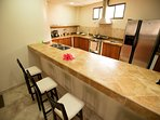 Sit on the bar stools while chatting with the cook in the kitchen.