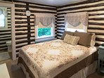 Bedroom with a queen bed and adjoining bathroom.