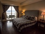Master w wood floors and king bed