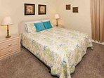 Carpeted guest bedroom with queen bed