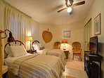 Fully furnished guest bedroom with flat screen TV and direct bathroom access.