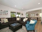 Living room with comfortable seating, opens to kitchen and dining room