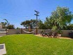 Large back yard features outdoor shower, surf boards, BBQ, seating around fire pit and hammock