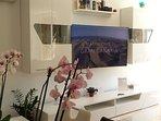 Smart tv Samsung, vitrina con copas de cristal, aire acondicionado, libros diferentes idiomas