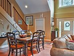 The front door opens up into a large space with an elegant dining table and a comfy living area.