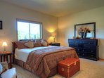 Master bedroom with ensuite bath, walk-in closet, and king bed