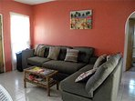 Bright coral colored living room area with new furniture. Cable wifi and games for entertainment.