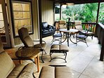 covered lanai (patio) with lounge chairs, sofa, table and chairs overlooking a man made waterfall