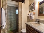 The downstairs guest bathroom features a single sink vanity and walk in shower.