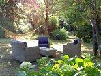 Salon de jardin et hamac sous la fraicheur des grands arbres