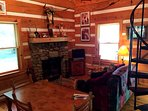 Living room area decorated in Native American motif with stone fireplace for evening fires.