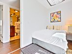 Third bedroom room features a full bed, skylight and access to balcony with outdoor seating .