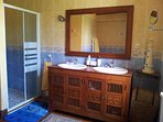 Large family bathroom with corner bath, walk-in shower and double basins. Separate toilet next door.