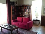 Library/second sitting room. Inglenook and patio doors to garden.