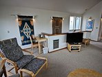 Upper level living room with a flat screen cable TV/VCR/DVD player, CD player, wood stove, hide-a-bed couch, two wicker...