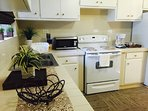 Full size kitchen with stove, refrigerator, microwave, coffee maker and tea kettle