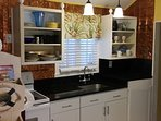 Granite counter tops,  brass antique walls, stainless steel fridge