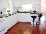 Custom kitchen with granite countertops, bar stools, two fridges and lots of cupboard space.