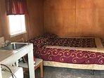 Inside cabin,queen bed, sink, refrig, chair