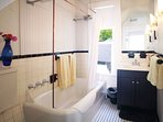 This black and white bathroom with a shower/tub is adjacent to 2 bedrooms on the 2nd floor