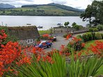 Crocosmia's line the front of Little Briar Cottage. View of the owners thatched cottage Loch Earn