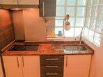 Detalle de la cocina de inducción, con todo lo necesario para cocinar: ollas, sartenes, menaje, etc.