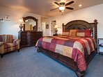 Master bedroom with en suite bath, ceiling fan, fireplace, and flat panel TV