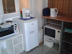 kitchenette with fridge stove microwave oven coffee machine , toaster as well as cooker