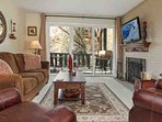 Beautiful living room with flat screen TV, wood burning fireplace and deck access.  Deck is equipped with table and...