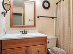 Guest bath, located outside bedroom 2, with single vanity and tub/shower combo.