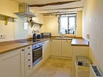 Separate well equipped kitchen with travertine floor