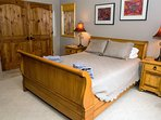 The sleigh bed room has large armoire on opposite wall
