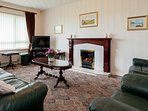 Spacious living room with Living Flame Gas Open Fire, SKY TV and comfortable seating.