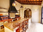 Kitchen island with travertine counters and seating for six serves the main dining area.