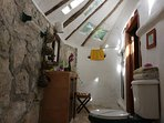 Casitas Kinsol Room #8 - The bathroom with a wall of stones and skylights on the roof