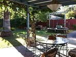 Gracious patio and backyard with lots of well-maintained trees, bushes, and and flowers.