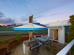 The outdoor entertaining area has a barbecue, fridge and large dining table.