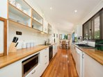 Large modern kitchen with cooking essentials and Nespresso coffee pod machine.