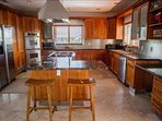 Large family kitchen with double ovens, dish washer, large refrigerator, microwave, toaster and coffeemaker accentuated...