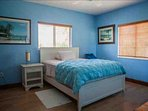 Second guest bedroom with a queen bed and tropical views