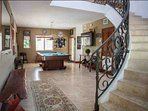 Sweeping staircase on the first floor, in the game / billiard room with a large, flat screen TV and outdoor bar...