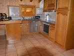 La cuisine ouverte sur le séjour avec lave-vaisselle, four, micro-ondes, etc.