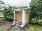 outdoor composting toilet with eco-cottage in background