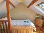 Upstairs are two bedrooms with exposed beams - this single leads through to the twin